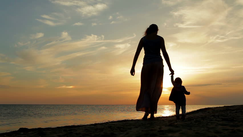 Mother with baby walking on sea coast. Silhouettes sunset.