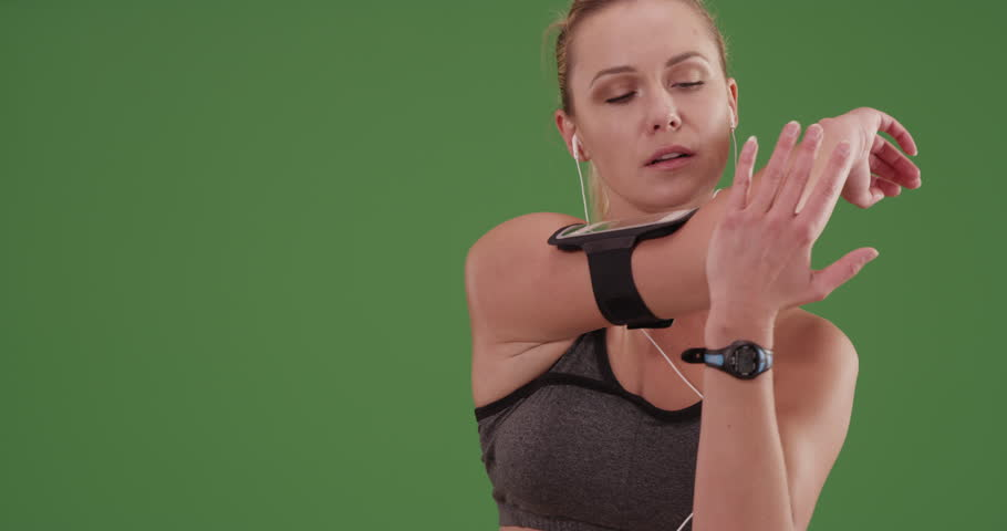 Woman runner stretching on green screen. On green screen to be keyed or composited.