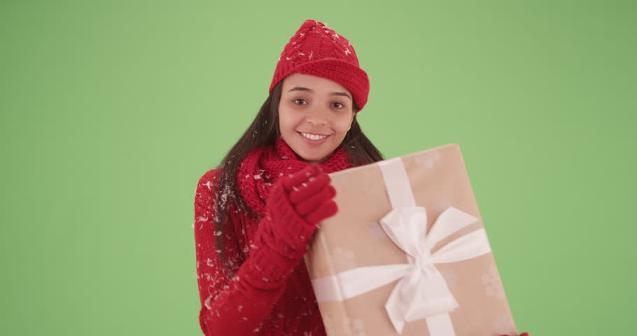 Hispanic girl showcasing a package in a red sweater on green screen. On green screen to be keyed or composited.