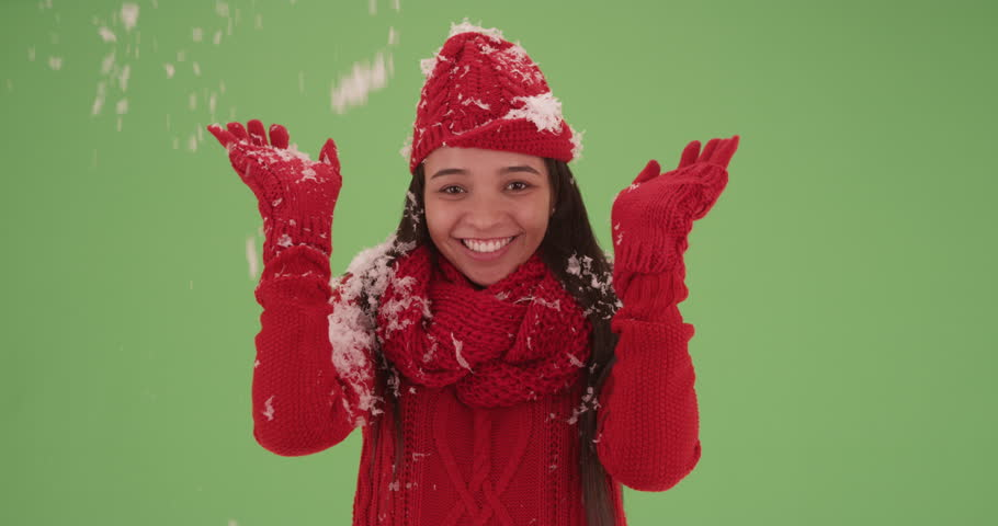 Laughing Latina girl in red winter clothes with snow falling on green screen. On green screen to be key or composited.