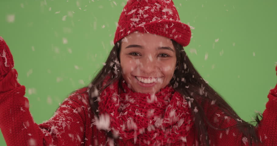 Close-up of a millennial Latina throwing snow in the air on green screen. On green screen to be keyed or composited.