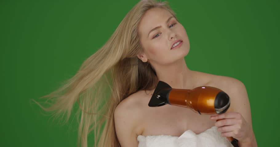 Caucasian girl blow dries and brushes her blonde hair on green screen. On green screen to be keyed or composited.