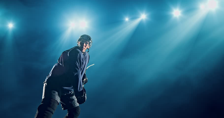 Ice Hockey player hits a puck on a dark background with intensional lens flares. He is wearing unbranded sports clothes.   Shutterstock Video #29841046