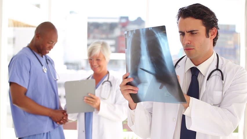 Smiling doctor looking at a chest x-ray in a bright office | Shutterstock HD Video #2984194