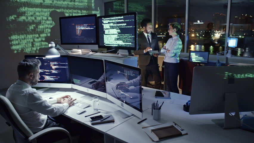 PAN of programmer typing computer code on multiply screen computer in dark office at night while African businessman working on tablet with female colleague; computer data reflecting on the wall | Shutterstock HD Video #29974147