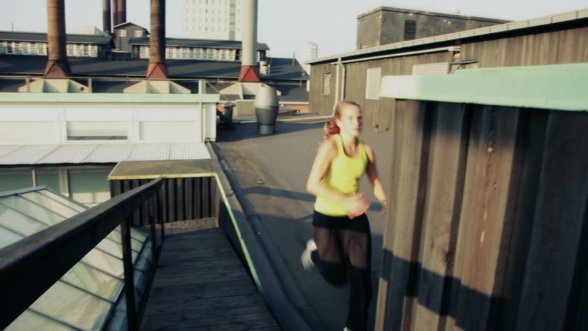 Handheld shot of female doing parkour or free running flow on rooftop. Urban sunset scene.