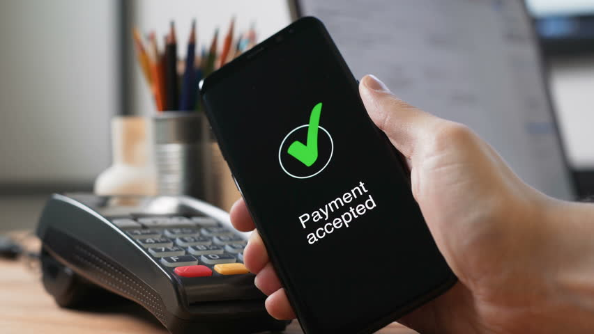 One male person pay in a trade with nfc system without contact in office. Close up shot man hold device with telephone app for banks payments use wireless. Process of transfering fund from cards
