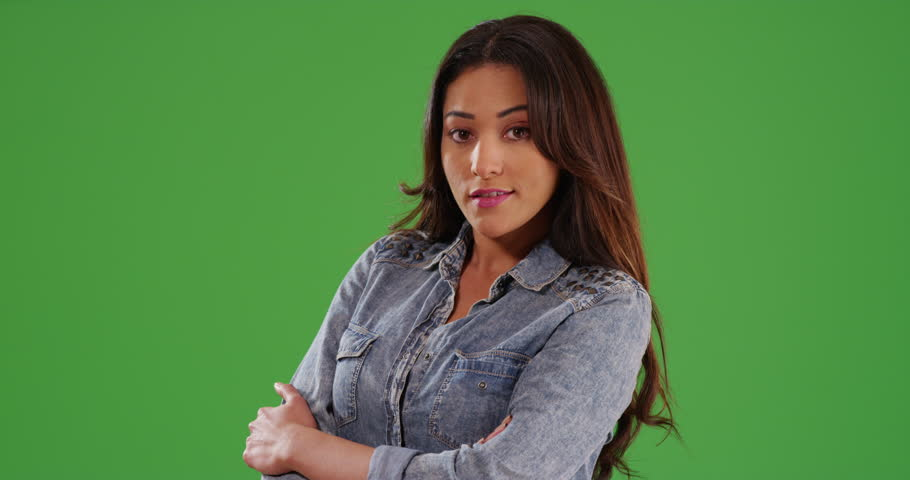 Portrait of beautiful Latina female standing laughing at camera on green screen. On green screen to be keyed or composited.