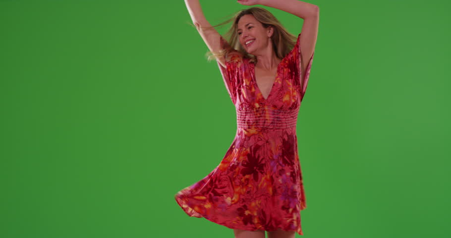 Attractive middle aged Caucasian woman dancing on green screen. On green screen to be keyed or composited.