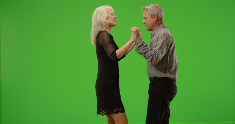Happy senior couple dancing together on green screen. On green screen to be keyed or composited.