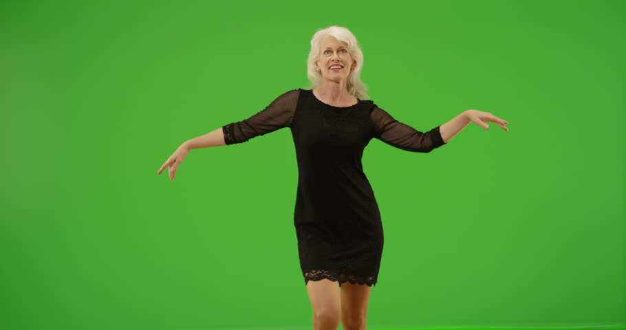 Happy senior woman dancing in a black dress on green screen. On green screen to be keyed or composited.