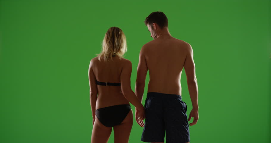 Sexy white millennial couple standing at the beach in contrasty lighting on green screen. On green screen to be keyed or composited.