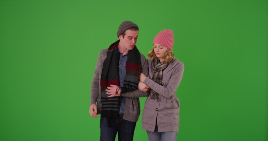 Young couple or close friends in winter clothes taking a walk outdoors, looking for destination using cell phone on green screen. On green to be keyed or composited.