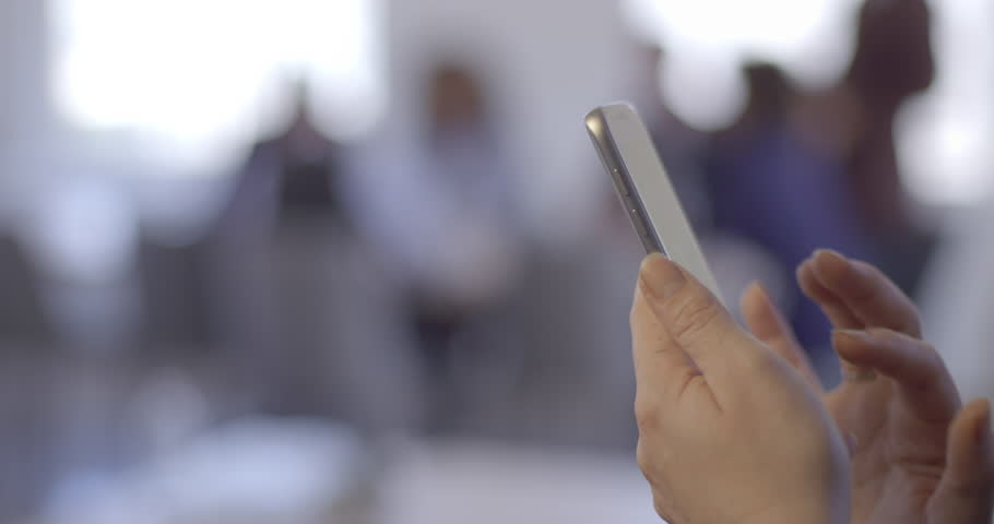 Woman's hand using a smart phone to look up information in front of soft focus office background. 4K. | Shutterstock HD Video #30143995