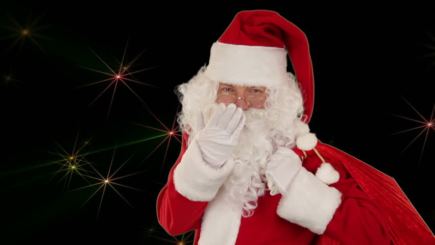 Santa Claus carrying his bag, is looking at the camera and sends a kiss with