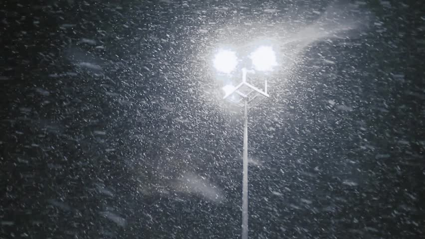 Snow falling with streetlight beams at night. Loop able snow fall background