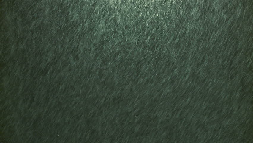 Snowfall at night time under a street light