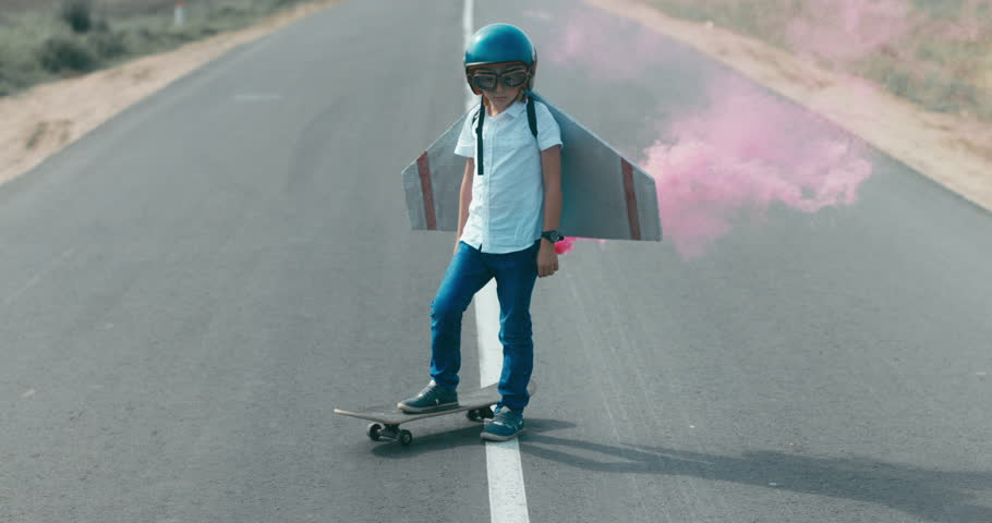 CINEMAGRAPH - seamless loop. Little boy wearing helmet and styrofoam wings standing on a skateboard on a rural road, pretending to be a pilot | Shutterstock HD Video #30858529