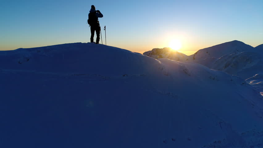 Aerial - Male mountaineer standing on top of snowy mountain and taking photos of beautiful winter scenery with his phone at sunset | Shutterstock HD Video #30940618