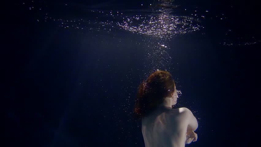 young naked woman is diving in deep dark water, underwater shot