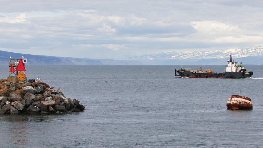 Large industrial landing craft leaving Homer Harbor, moving past the breakwater