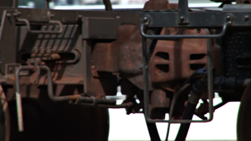 Close-up of a hitch coupler as a freight train of tank cars rolls by.