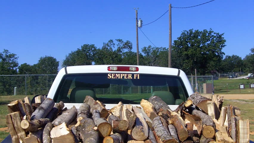 A rick of firewood in the back of a pickup truck.