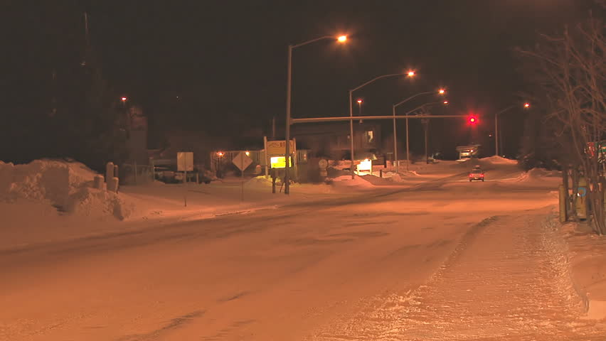 Minimal traffic at night in a small town on snow-covered roads in the middle of