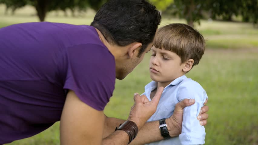 Young people and difficult parenting, upset father scolding scared son while holding his arm. Medium and wide shot in sequence