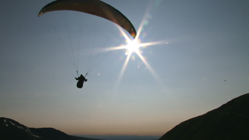 Almost like floating in space, a paraglider moves smoothly through the air,