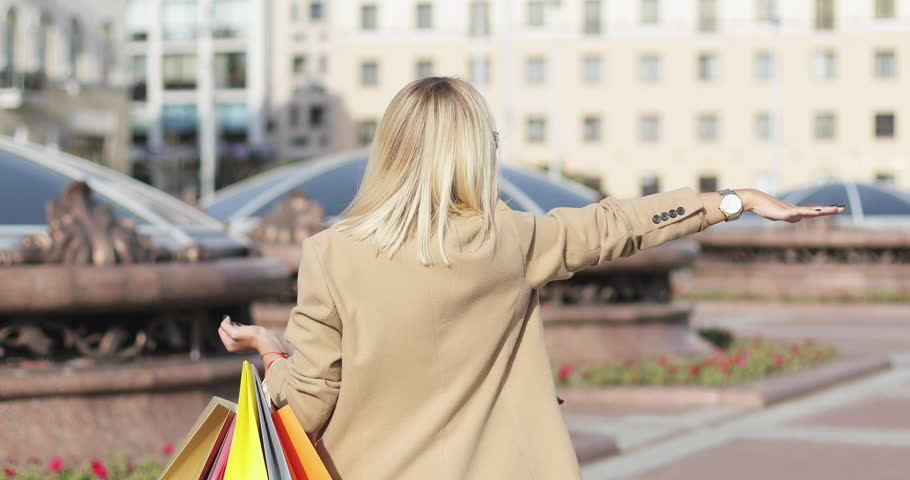Back view beautiful blonde caucasian woman in sunglasses waving hand to stop the car that is passing by. Hitch-hiking. The building and the sidewalk on the background. | Shutterstock HD Video #31205098