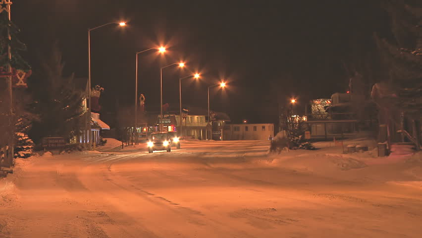 HOMER, AK - CIRCA 2011: Minimal traffic at night in a small town on snow-covered