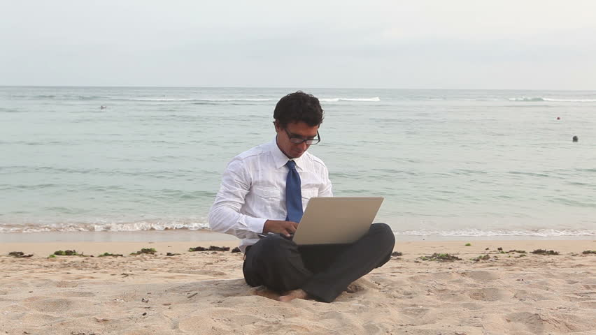 young businessman working on laptop on the beach