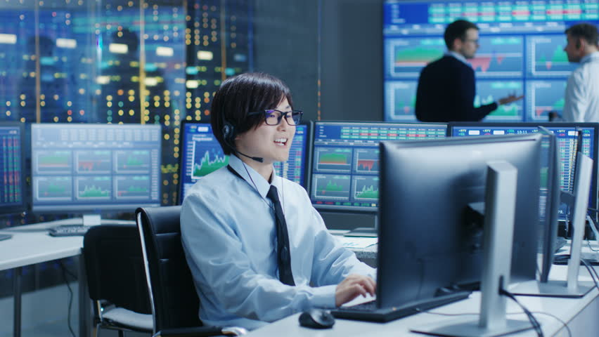 In the Network Operations Center Trader Makes Personal Client Call with a Headset. In the Background Traders Discuss Data Shown on Monitors.  | Shutterstock HD Video #31689613