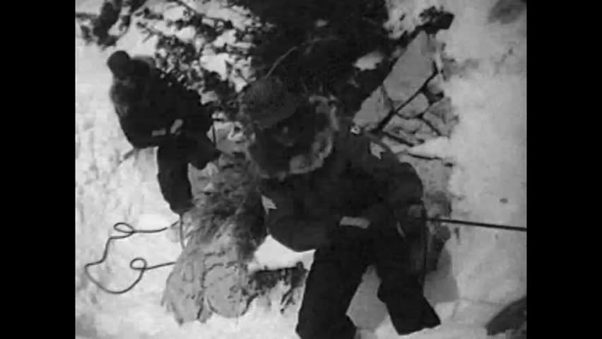 CIRCA 1960s - Hand grenades and explosive charges are used to trigger an avalanche on a show-covered mountain range, in 1965.