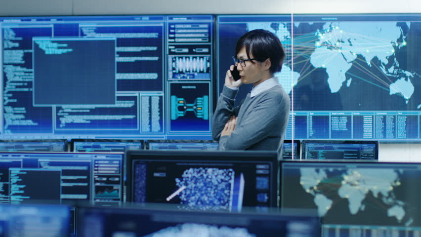In the System Control Room IT Administrator Talks on the Phone. He's in a High-Tech Facility That Works on the Surveillance, Neural Networks, Data Mining, AI Projects. Shot on RED EPIC-W 8K Camera. | Shutterstock HD Video #31712077