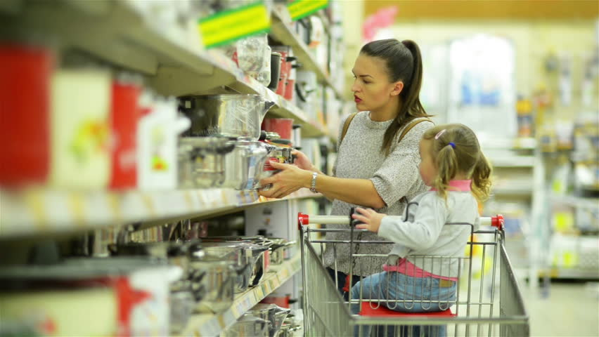 Happy Female Child and Her Attractive Mother Inside the Hypermarket Choosing Some Dishes or Pans Together Standing near Supermarket Shelf. | Shutterstock HD Video #31775371