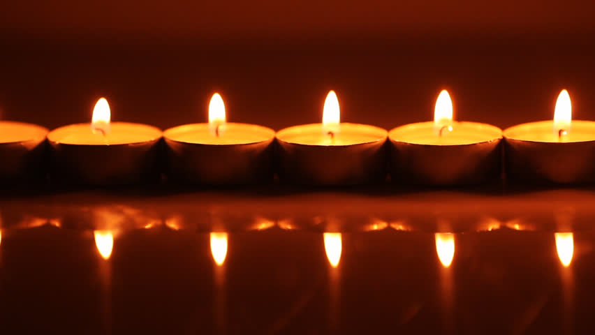 Small Candles Burning With A Blend Of Colorful Bokeh