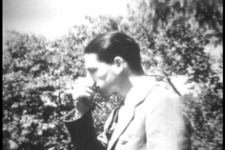 CIRCA 1930s Universal newsreel shows man who smokes cigarettes through his ears.