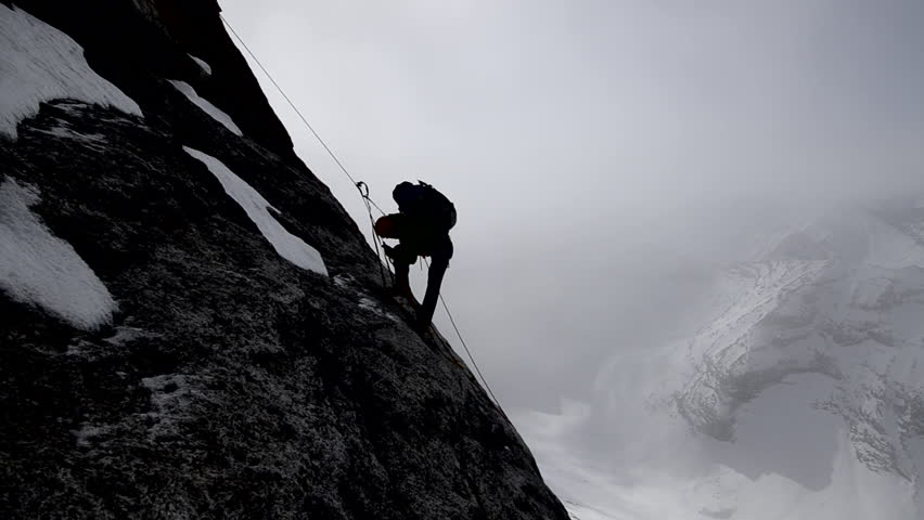 Silhouette of a climber with a backpack ascending a sheer rock face on his way to a mountain peak in the Alaskan wilderness during the day