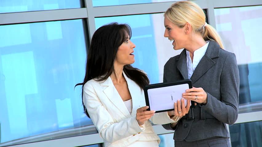 Two smart female city businesswomen outside a modern office building using a wireless tablet | Shutterstock HD Video #3206734