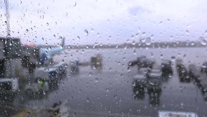 Raindrops hitting a window at the Ottawa International Airport, Air Canada A-321 in soft focus