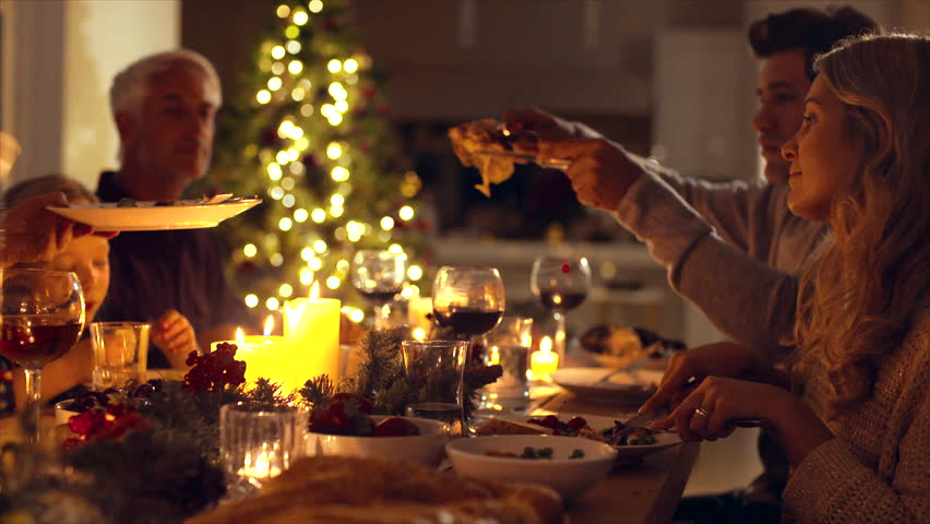 Christmas eve dinner, family sitting at dining table enjoying dinner together. Family celebrating christmas together at home.   Shutterstock Video #32352271