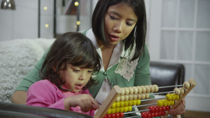 A loving mother of Asian ethnicity is teaching her cute little daughter to count with the use of an abacus. In slow motion