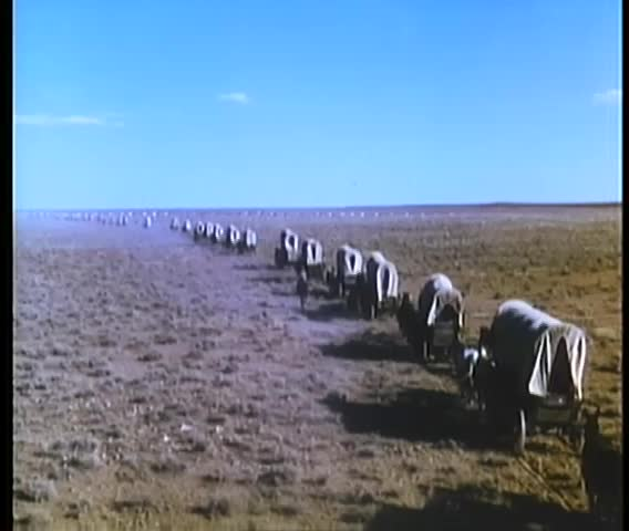 Montage of covered wagons and settlers traveling cross country