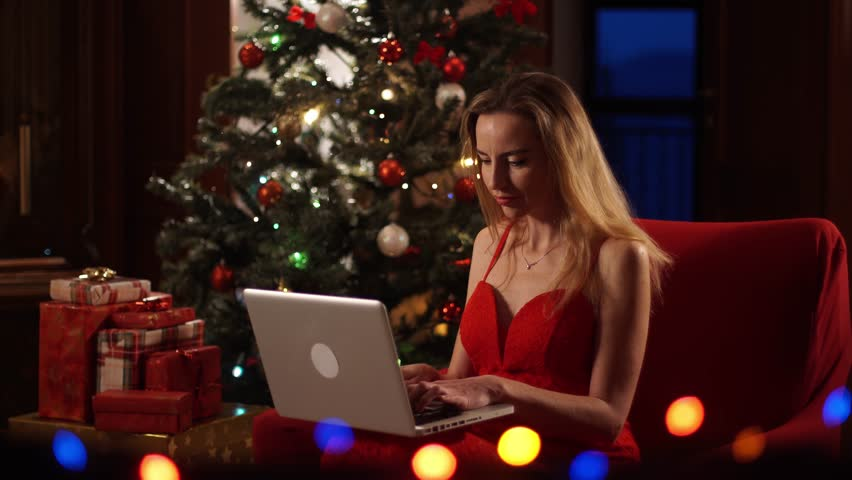 Beautiful girl surfing the internet on her laptop computer for Christmas bargains, internet technology, dolly shot | Shutterstock HD Video #32720293