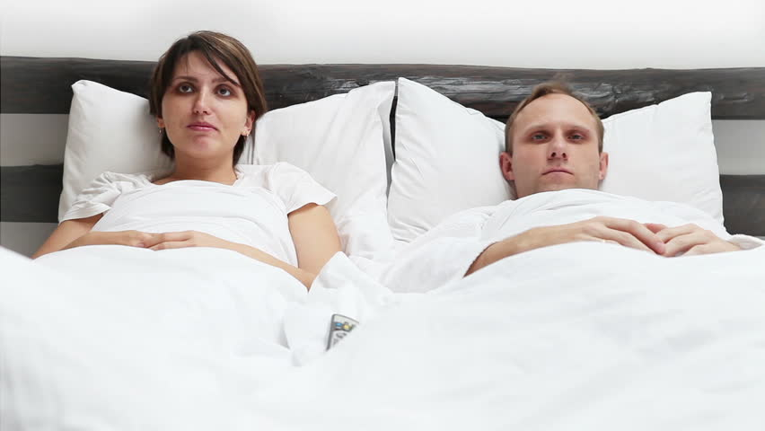 Wife and Husband TV Remote control conflict in Bed   HD stock footage clip. Relationship Difficulties  Couple Sitting In Park Stock Footage