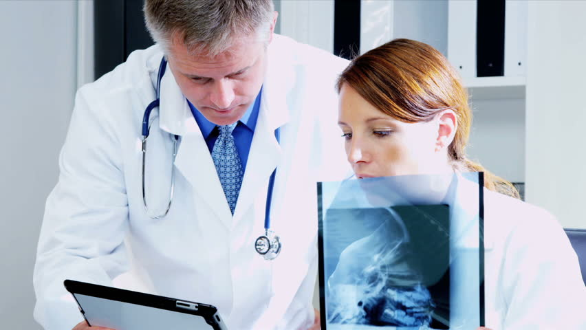 caucasian male female medical colleagues consulting over patient x ray results with computer screen shot - Epic Consultant