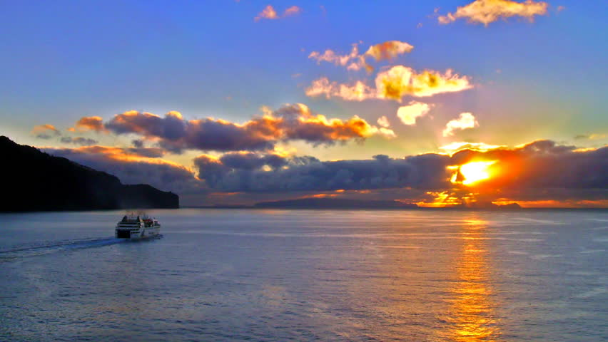 High definition time lapse of a ship sailing into the sunrise.