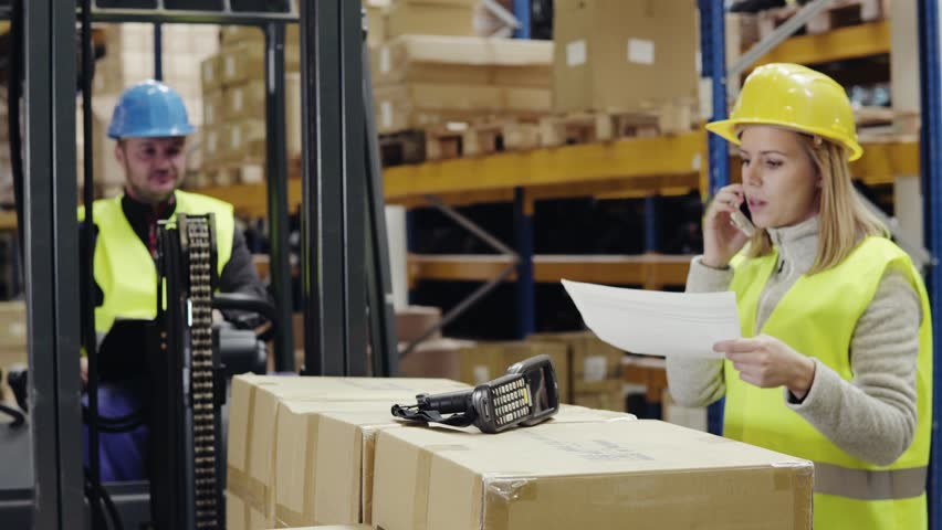 Young workers with smartphone and forklift in warehouse. | Shutterstock HD Video #33090724